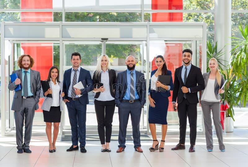 Los hombres de negocios agrupan la línea derecha en la oficina moderna, fila de la sonrisa feliz de los empresarios fotografía de archivo libre de regalías