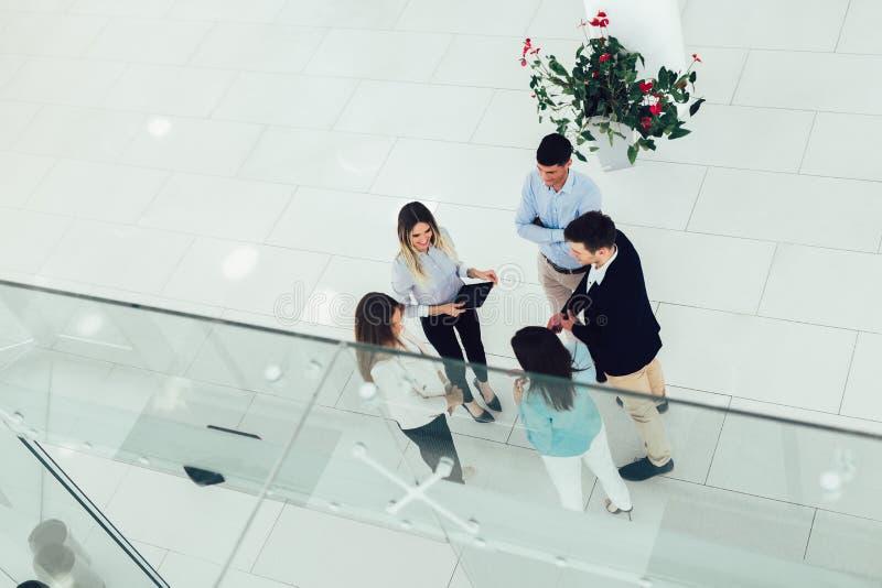Los hombres de negocios agrupan la sonrisa feliz que se coloca en la opini?n superior de la oficina moderna imagen de archivo libre de regalías