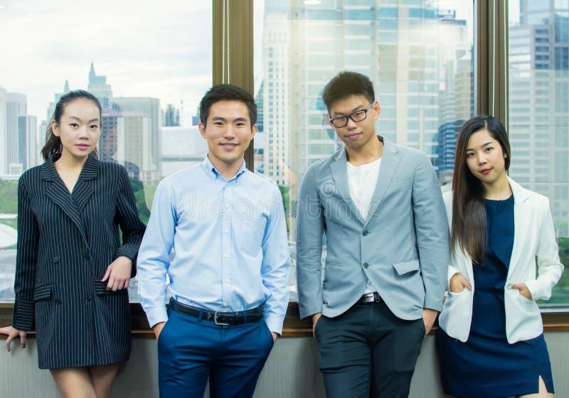 Los hombres de negocios asiáticos están presentando al lado de la ventana imagenes de archivo