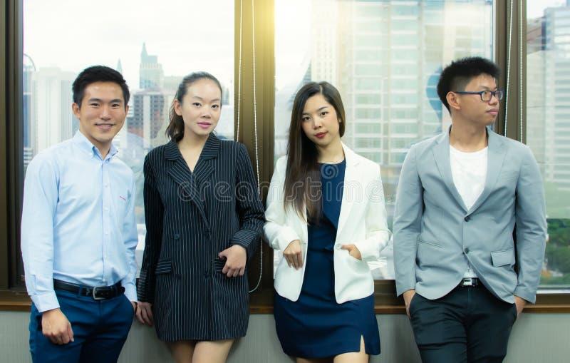 Los hombres de negocios asiáticos están presentando al lado de la ventana imagen de archivo