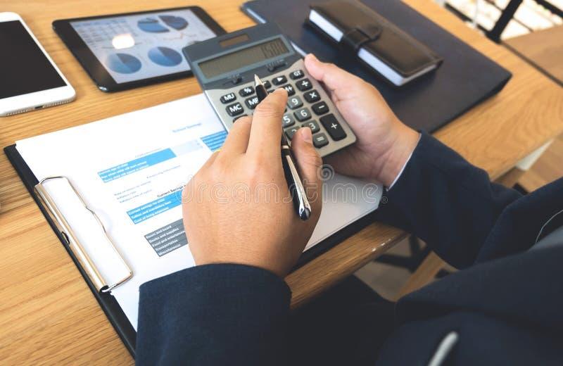 Los hombres de negocios calculan la renta del negocio de exportaci?n en la tabla de madera Concepto del asunto foto de archivo