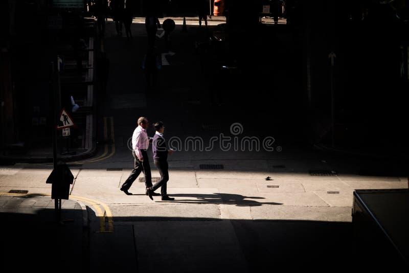 Los hombres de negocios caminan a través de un pequeño empalme en el callejón trasero de Hong Kong imagenes de archivo