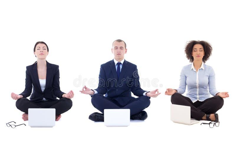 Los hombres de negocios cansados que se sientan en yoga presentan con los ordenadores portátiles aislados fotografía de archivo