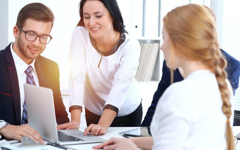 Los hombres de negocios combinan en reunirse en oficina Foco en la mujer de negocios que señala en el ordenador portátil Trabajo  fotografía de archivo