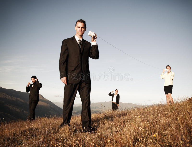 Los hombres de negocios comunican concepto del teléfono de la taza de papel al aire libre imagenes de archivo
