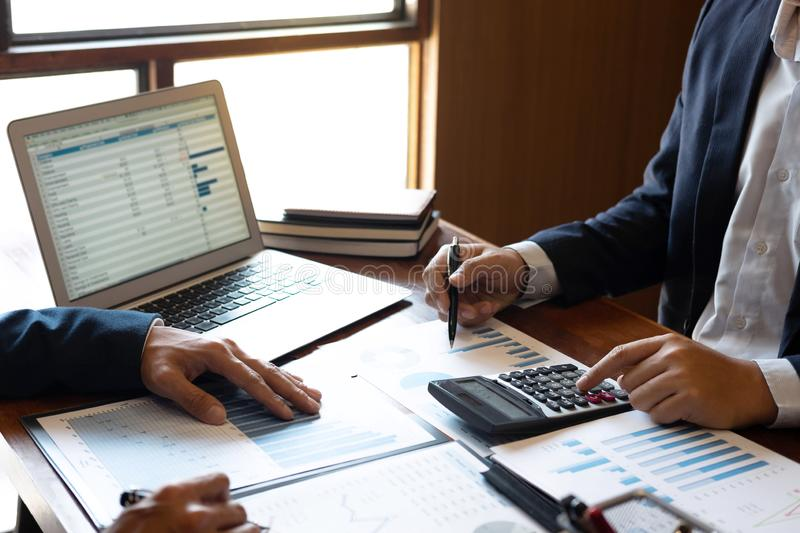 Los hombres de negocios del equipo discuten en reunirse al funcionamiento del proyecto de inversi?n y a la estrategia de planific fotografía de archivo libre de regalías