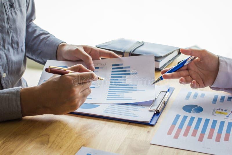 Los hombres de negocios del punto de reunión a discutir, planean y trazan la subida y la caída de económico en el fondo blanco foto de archivo libre de regalías