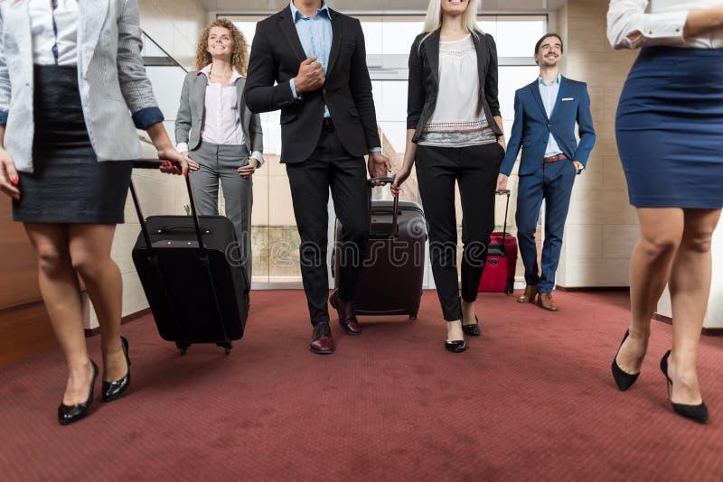 Los hombres de negocios en pasillo del hotel, huéspedes del grupo de los empresarios de la raza de la mezcla llegan imagenes de archivo