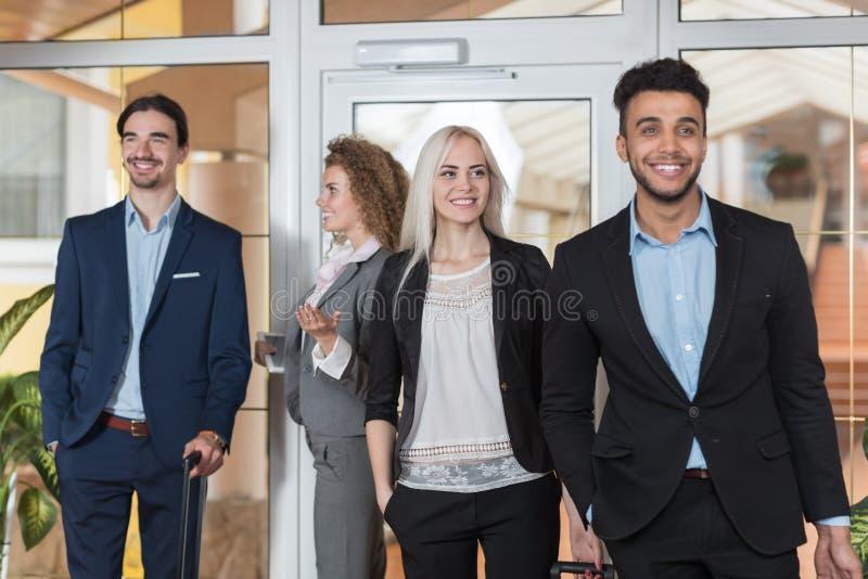 Los hombres de negocios en pasillo del hotel, huéspedes del grupo de los empresarios de la raza de la mezcla llegan imagen de archivo