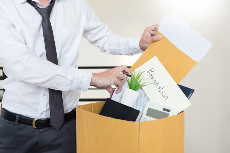 Los hombres de negocios están llevando a cabo el documento de la dimisión y a la compañía personal que embala en el trabajo cambi imágenes de archivo libres de regalías