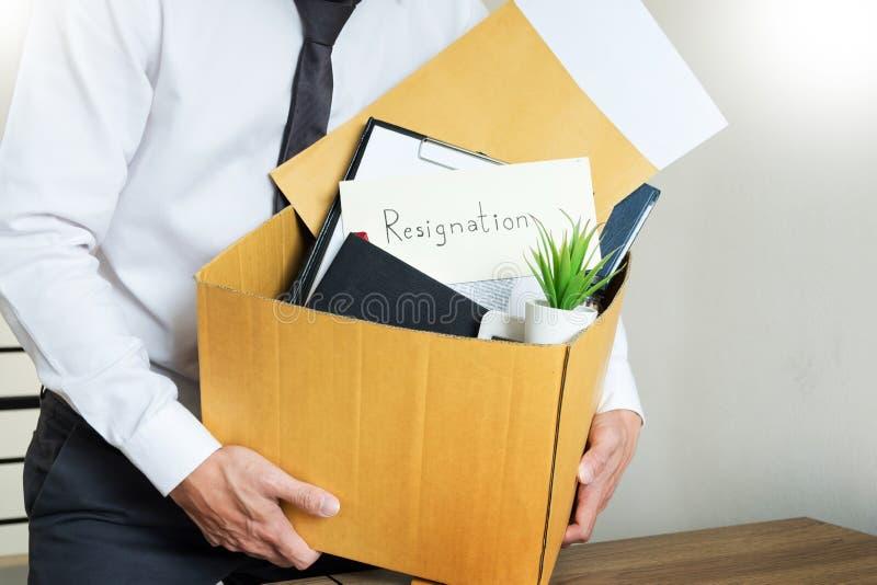 Los hombres de negocios están llevando a cabo el documento de la dimisión y a la compañía personal que embala en el trabajo cambi fotos de archivo libres de regalías
