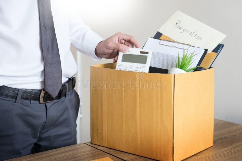 Los hombres de negocios están llevando a cabo el documento de la dimisión y el personaje que embala fotos de archivo