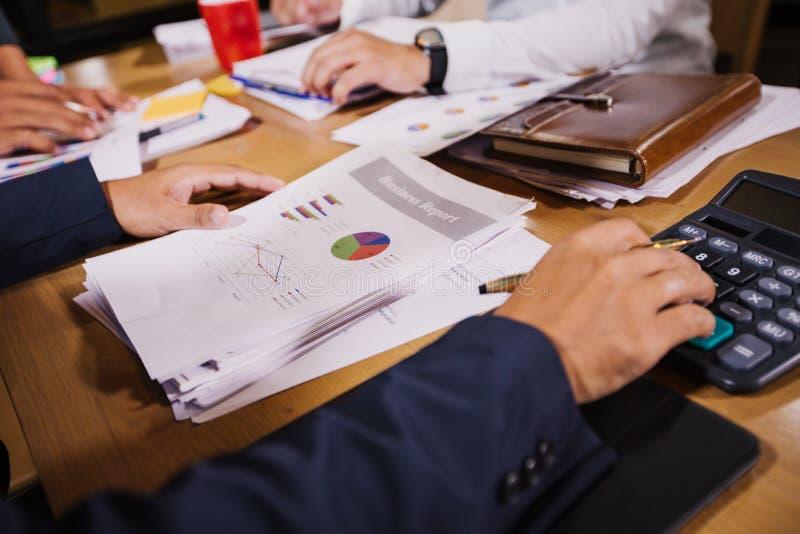 Los hombres de negocios están utilizando las calculadoras y los datos de negocio del análisis y y representan el funcionamiento f imagenes de archivo