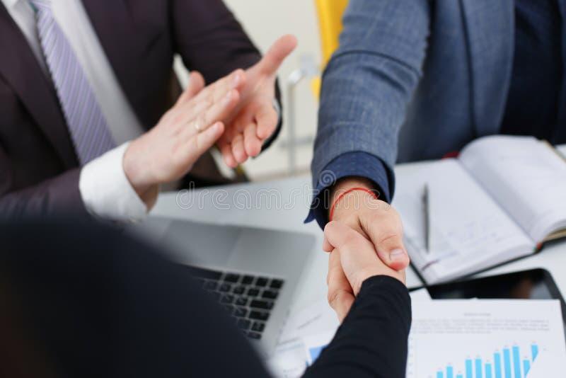 Los hombres de negocios felices jovenes hacen que la reunión en oficina sacuda las manos con uno a imagen de archivo libre de regalías