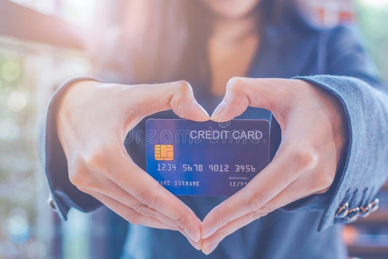 Los hombres de negocios femeninos están sosteniendo una tarjeta de crédito y están haciendo una mano en forma de corazón imágenes de archivo libres de regalías