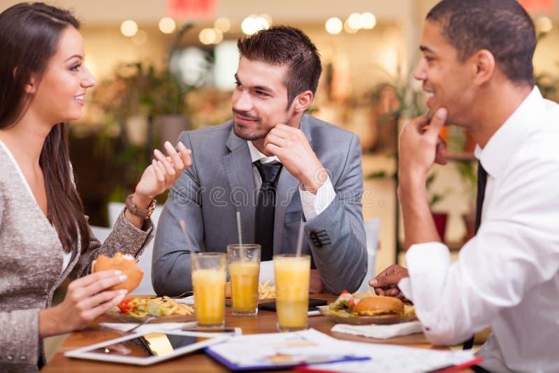 Los hombres de negocios gozan en almuerzo en el restaurante imágenes de archivo libres de regalías