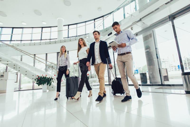 Los hombres de negocios hablan y caminan así como la tableta y el equipaje digitales de la tableta fotos de archivo