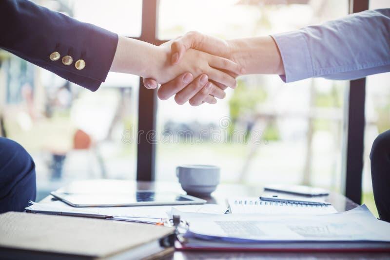 Los hombres de negocios hacen un trato con el apretón de manos en la oficina o el café Su fotografía de archivo libre de regalías