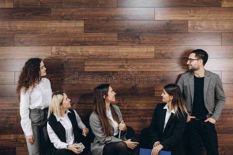 Los hombres de negocios hermosos están utilizando el ordenador y están sonriendo mientras que trabajan en oficina foto de archivo