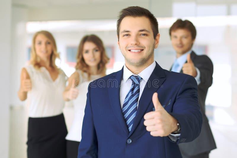 Los hombres de negocios jovenes acertados que muestran los pulgares suben la muestra foto de archivo libre de regalías