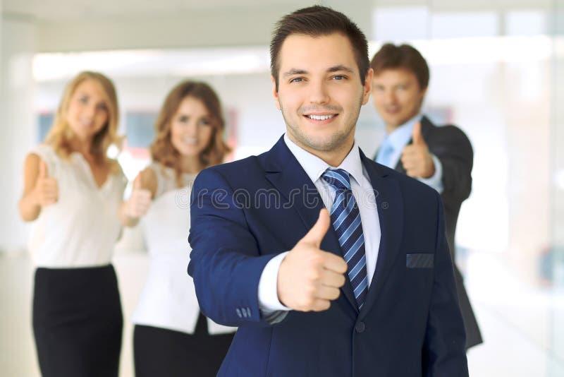 Los hombres de negocios jovenes acertados que muestran los pulgares suben la muestra imagenes de archivo