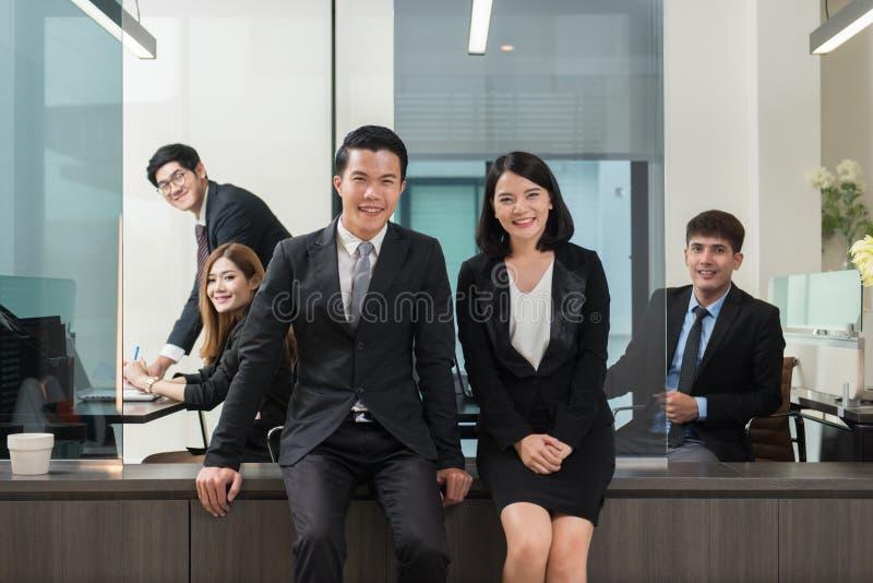 Los hombres de negocios jovenes del grupo tienen la reunión y funcionamiento en la oficina interior imagenes de archivo