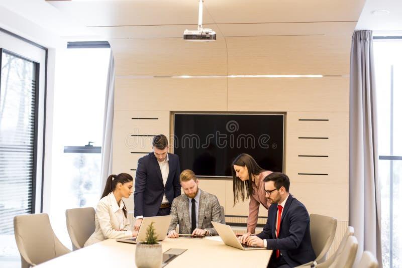 Los hombres de negocios jovenes tienen reunión en una oficina moderna foto de archivo