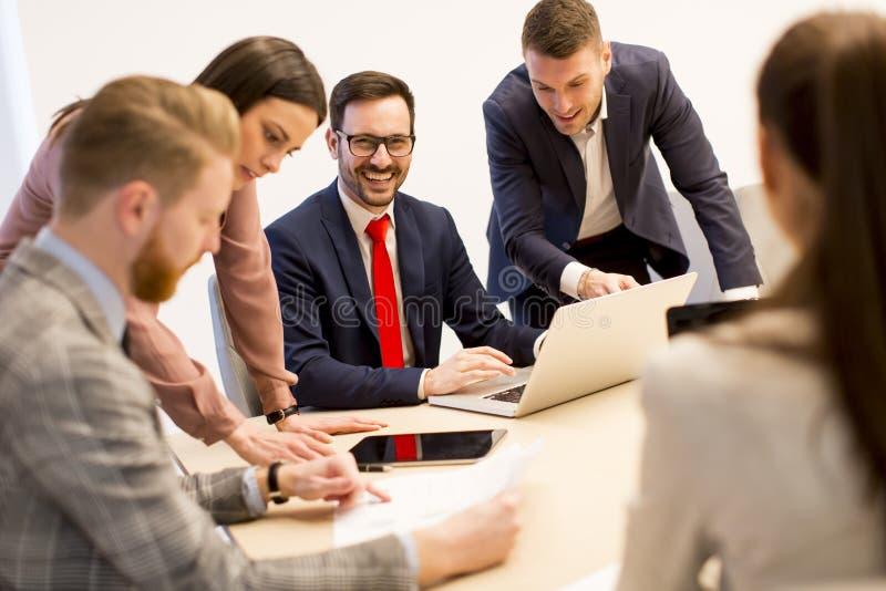 Los hombres de negocios jovenes tienen reunión en una oficina moderna foto de archivo libre de regalías
