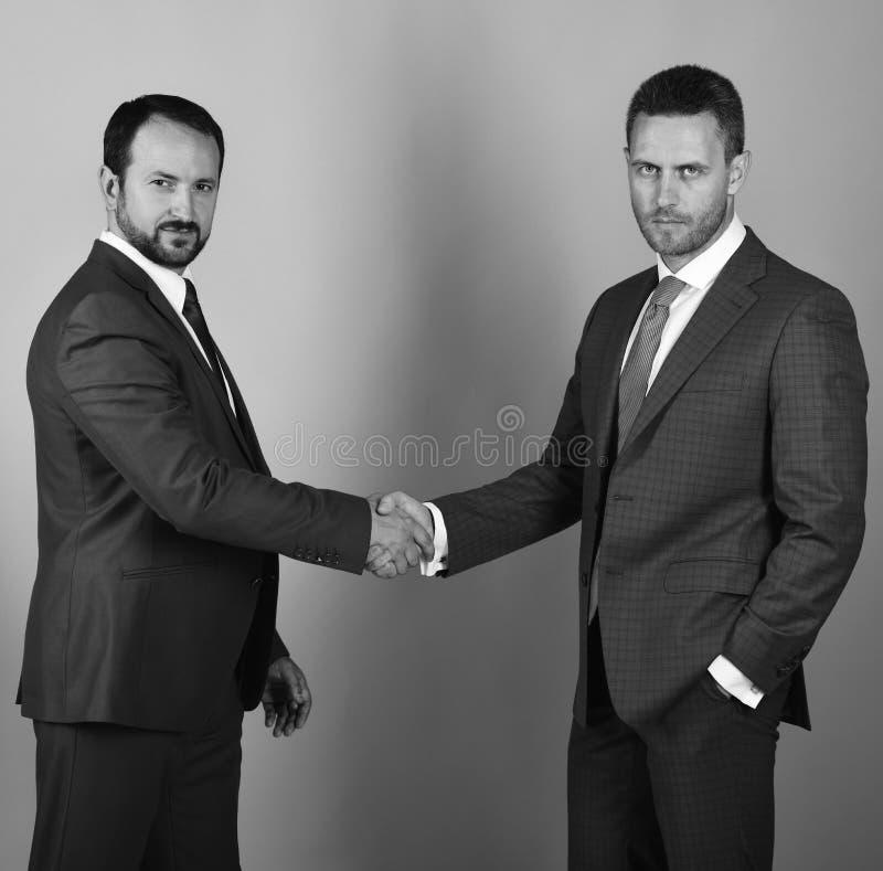 Los hombres de negocios llevan los trajes y los lazos elegantes Los hombres con la barba y las caras serias hacen trato o el acue foto de archivo libre de regalías