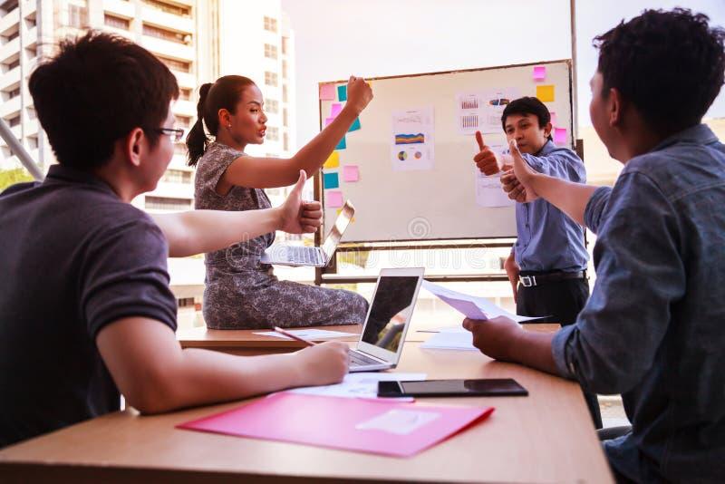 Los hombres de negocios manosean con los dedos para arriba sobre la tabla en una reunión de planificación en la oficina moderna T imagen de archivo