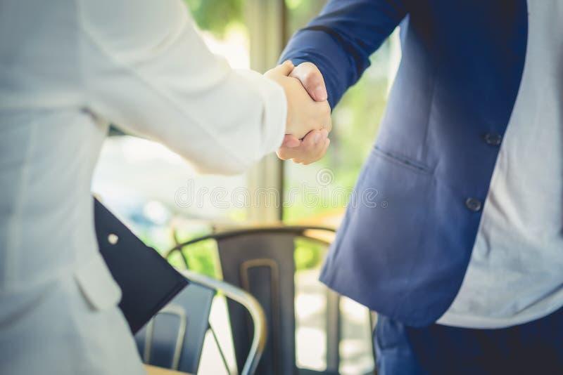 Los hombres de negocios masculinos y femeninos son apretón de manos acuerdan unirse al busi fotografía de archivo