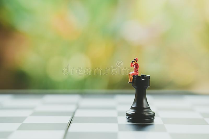 Los hombres de negocios miniatura de la gente que se sientan en análisis del ajedrez comunican sobre estrategia empresarial O pla foto de archivo libre de regalías