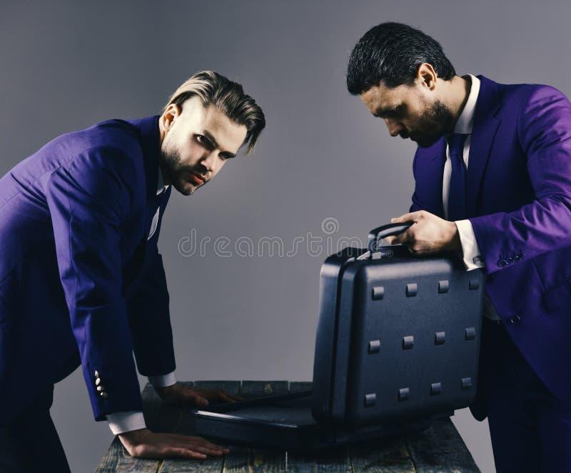 Los hombres de negocios miran en la cartera abierta en fondo oscuro imágenes de archivo libres de regalías
