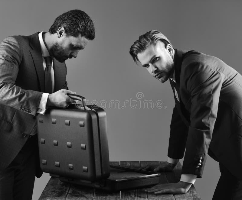 Los hombres de negocios miran en la cartera abierta en fondo oscuro foto de archivo