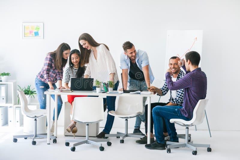 Los hombres de negocios o los estudiantes jovenes trabajan en el equipo interior imagenes de archivo