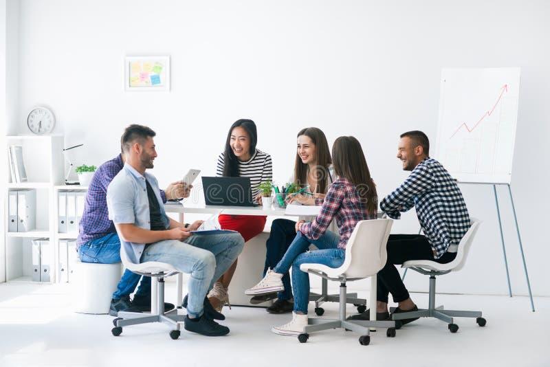 Los hombres de negocios o los estudiantes jovenes trabajan en el equipo interior imagen de archivo libre de regalías