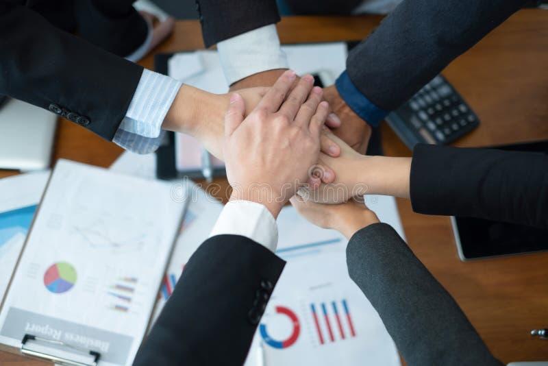 Los hombres de negocios pusieron sus manos juntas empresarios que celebran en el negocio del trato del éxito de la oficina, conce imagen de archivo