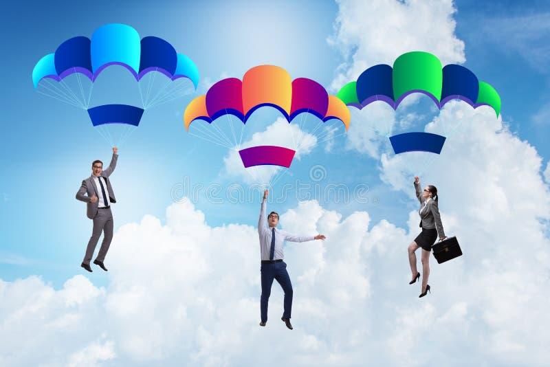 Los hombres de negocios que caen abajo en los paracaídas imagenes de archivo