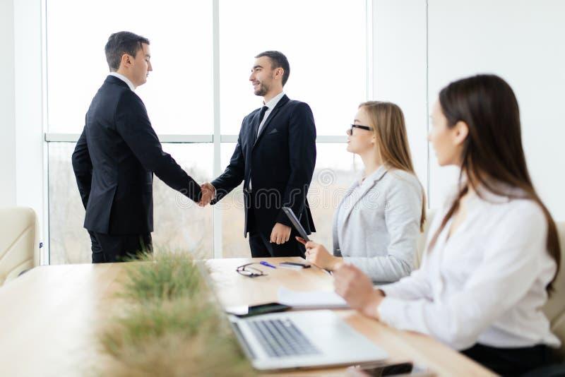 Los hombres de negocios que el apretón de manos consigue están de acuerdo la muestra del contrato en sala de reunión foto de archivo libre de regalías