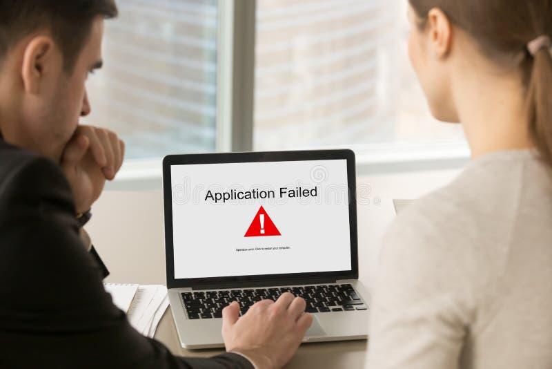 Los hombres de negocios que miraban la pantalla del ordenador portátil con el uso fallaron imágenes de archivo libres de regalías