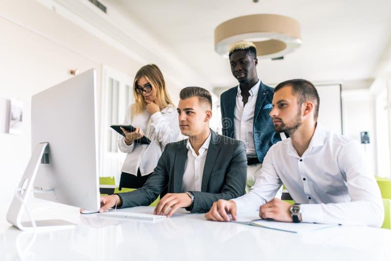 Los hombres de negocios que muestran al equipo trabajan mientras que trabajan en sala de juntas en interior de la oficina Gente q imagen de archivo