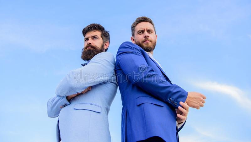 Los hombres de negocios retroceden para apoyar el fondo del cielo azul El aspecto impecable mejora al empresario del profesional  imagen de archivo