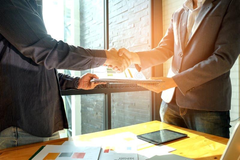 Los hombres de negocios sacuden las manos al entrar en negocio, en foto de archivo