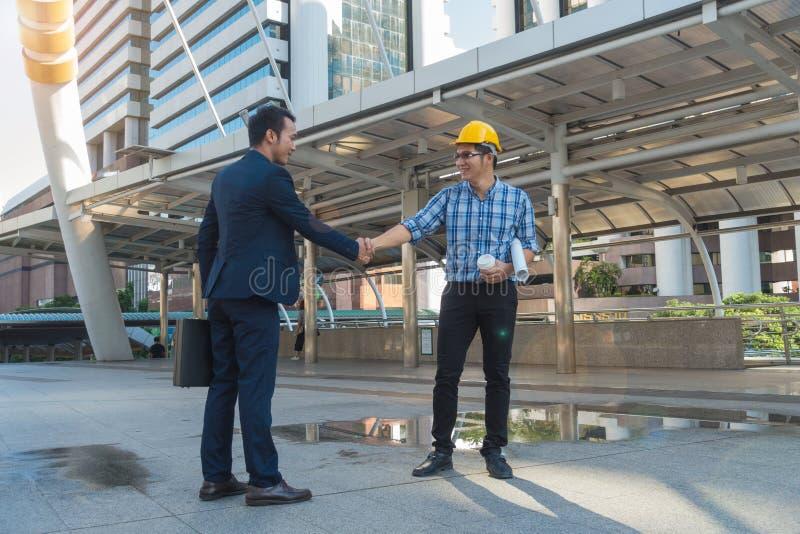 Los hombres de negocios sacuden las manos con un ingeniero joven en la ciudad imagen de archivo libre de regalías