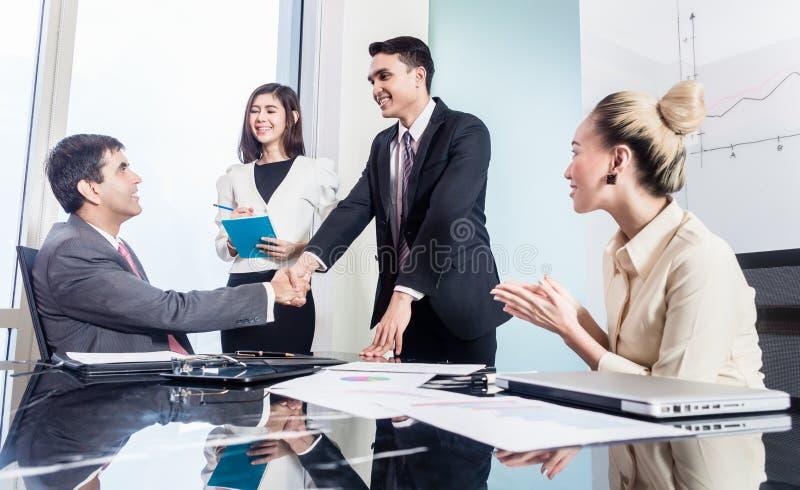 Los hombres de negocios sacuden las manos después de trato acertado imagen de archivo