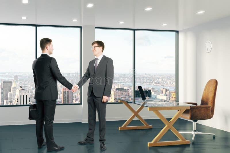 Los hombres de negocios sacuden las manos en oficina moderna con la opinión de la ciudad imagen de archivo