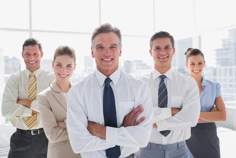 Los hombres de negocios sonrientes con los brazos cruzaron en su oficina foto de archivo