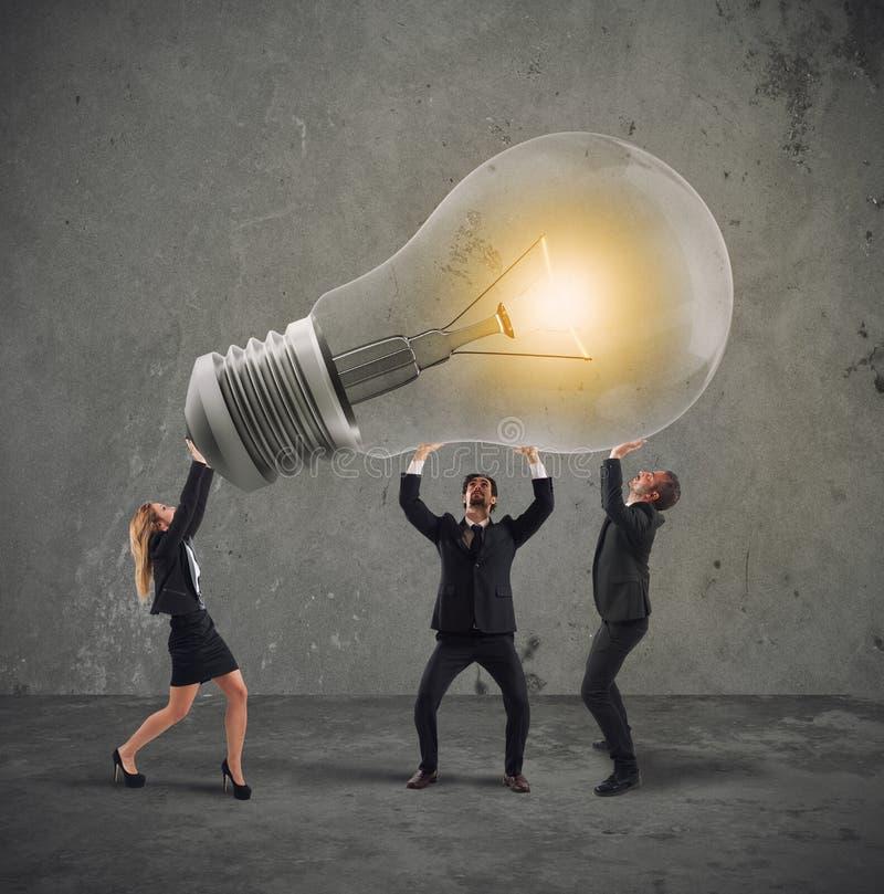 Los hombres de negocios sostienen una bombilla concepto de nuevo inicio de la idea y de la compañía imágenes de archivo libres de regalías