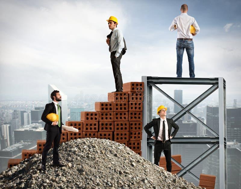 Los hombres de negocios trabajan juntos para construir un edificio foto de archivo libre de regalías