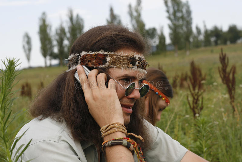 Los hombres del hippie hablan en el teléfono móvil fotografía de archivo